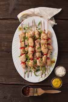 건강한 바베큐. 야채와 허브를 곁들인 치킨 케밥, 여름 피크닉을위한 수분이 많은 맛있는 간식