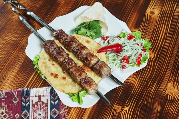 Healthy barbecued lean cubed pork kebabs served with a corn tortilla and fresh lettuce and tomato salad, close up view