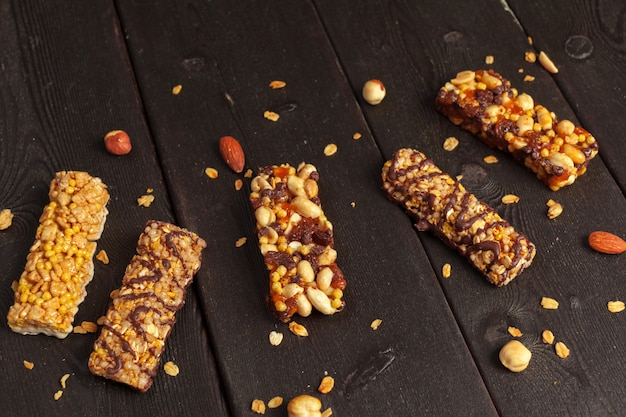 Healthy bars with nuts, seeds and dried fruits on the wooden table