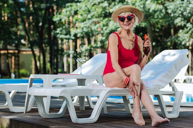 Healthy beaming retired woman wearing straw hat getting suntan while sitting on deck chair