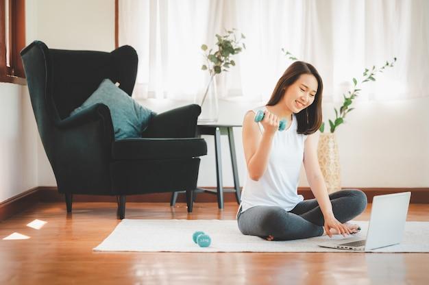 Здоровая красивая азиатская женщина сидит на полу, держа гантели, используя ноутбук дома в гостиной, готовой к тренировке