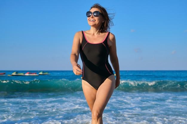 海岸沿いを歩くサングラス水着で健康的な美しい中年女性。ビーチリゾート、青い空の波の夕日の背景でリラックスして幸せな女性の笑顔