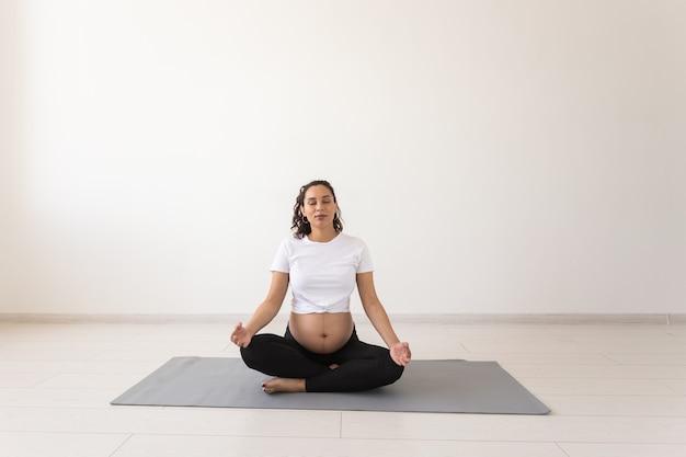 건강 한 아름 다운 임산부 요가 수업 전에 명상 하 고 바닥에 매트에 앉아있는 동안 이완. 출산을위한 신체의 육체적 정신적 준비의 개념. copyspace