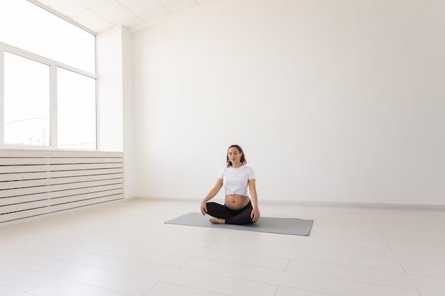 健康な美しい妊婦は、ヨガのクラスの前に瞑想し、マットの上に座ってリラックスします