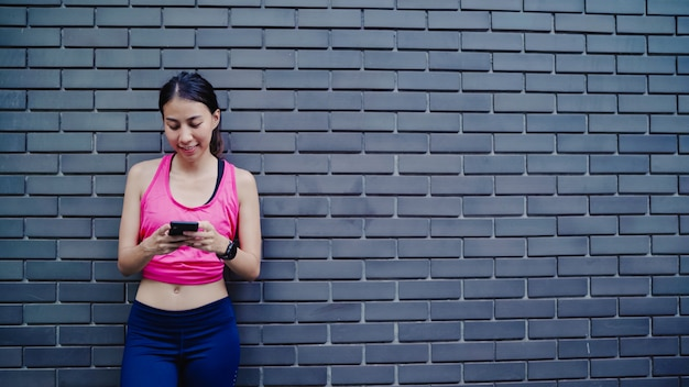 Healthy beautiful young asian athlete woman using smartphone for checking social media