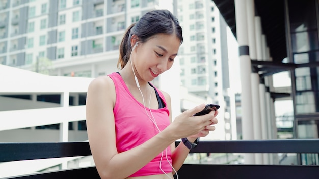 Healthy beautiful young asian athlete woman using smartphone for listen to music while running