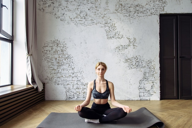 Healthy and beautiful young woman sitting at home in yoga position.