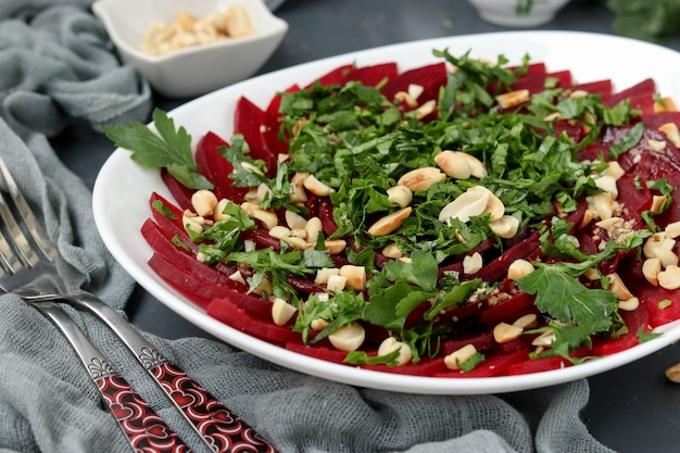 Healthy beetroot salad with peanuts and parsley on a white plate