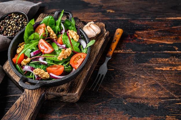 Здоровый зеленый салат бистро с миксом листьев мангольда, швейцарского мангольда, шпината, рукколы и орехов на сковороде. темный деревянный фон. вид сверху. скопируйте пространство.