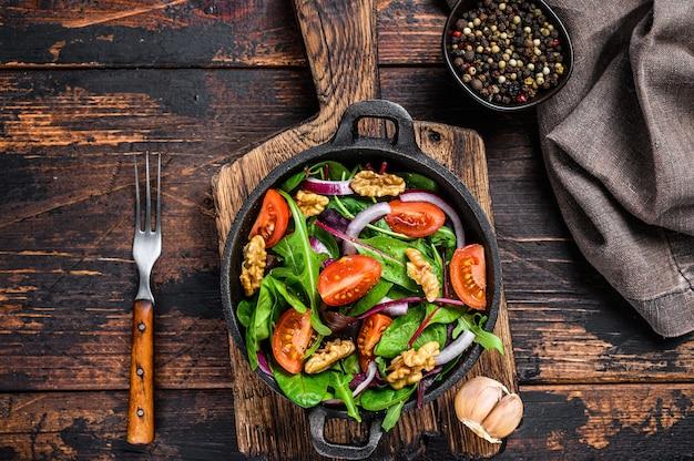 믹스를 곁들인 건강한 비스트로 그린 샐러드는 망골드, 스위스 차드, 시금치, 아루굴라, 견과류를 팬에 남깁니다. 어두운 나무 배경입니다. 평면도.