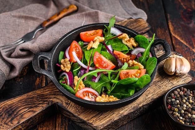 Здоровый зеленый салат-бистро с листьями мангольда, швейцарским мангольдом, шпинатом, рукколой и орехами на сковороде