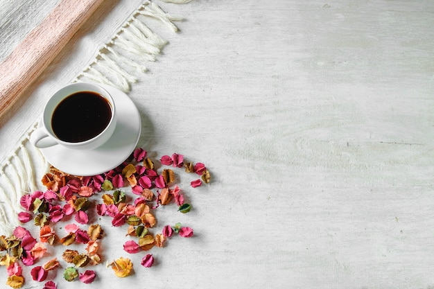A healthy black coffee cup and dried flowers are placed on a white table.