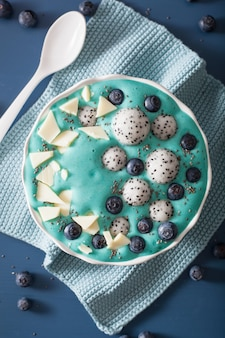 Healthy blue spirulina smoothie bowl with blueberry, white chocolate, dragon fruit, chia seed