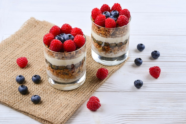 Healthy blueberry and raspberry parfait in a glass on a rustic white wood