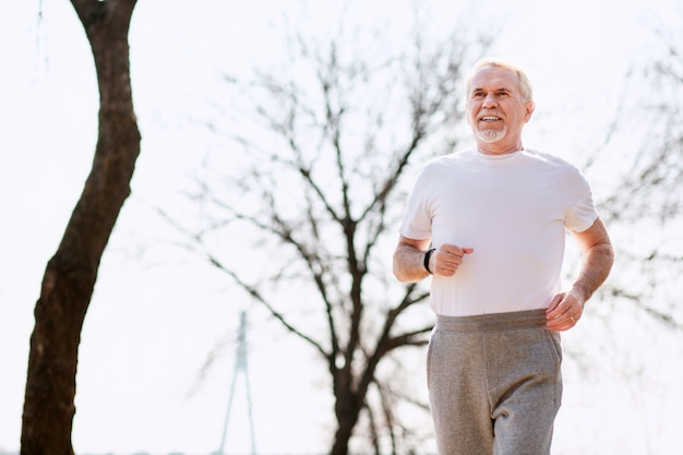 Healthy body. low angle of appealing mature man running in park while controlling breath