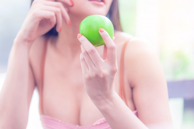 Healthy body woman holding a green apple for healthy and body shape diet healthy eating concept.
