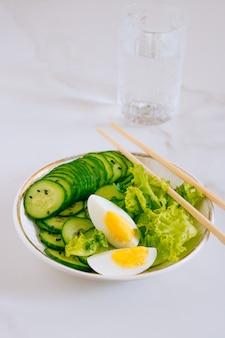 健康的なボウル、卵と大理石の背景に水の入ったグラスキュウリのサラダ