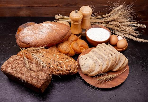 健康的なパンの品揃え。ベーカリー製品。さまざまなロールパン。木の表面に穀物パンや焼き菓子を集めました。ショッピング食品スーパーマーケットのコンセプト。小麦とライ麦粉から作られたパン。