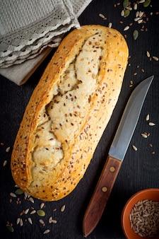 古い木製の背景にふすま、ヒマワリの種、カボチャ、亜麻、ゴマの種と健康的なパン。