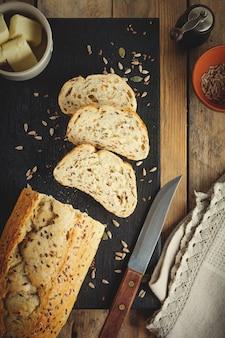 오래 된 나무 표면에 밀기 울, 해바라기 씨, 호박, 아마, 참깨와 함께 건강 한 빵. 평면도. 선택적 초점 톤 이미지.