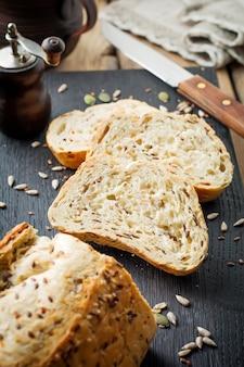 Здоровый хлеб с отрубями, семенами подсолнечника, тыквой, семенами льна и кунжута на старой деревянной поверхности