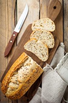 오래 된 나무 표면에 밀기울, 해바라기 씨, 호박, 아마, 참깨와 함께 건강한 빵