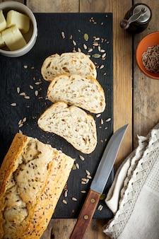 古い木の表面にふすま、ヒマワリの種、カボチャ、亜麻、ゴマの種が付いた健康的なパン