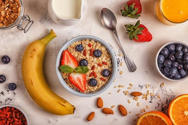 Здоровый завтрак - тарелка овсянки, ягод и фруктов, апельсинового сока и молока.