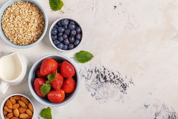 Здоровый завтрак - миска овсянки, ягод и фруктов, вид сверху.