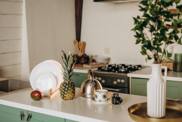 ヘルシーな朝食、新鮮なグレープフルーツ、マンゴー、パイナップルの白い料理、コーヒーティー。ソフトセレクティブフォーカス。