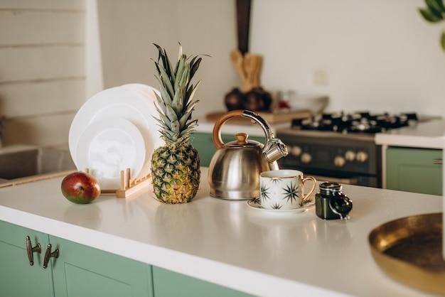 ヘルシーな朝食、新鮮なグレープフルーツ、マンゴー、パイナップルの白い料理、コーヒーティー