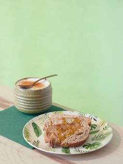 シナモンパウダーと全粒粉パントーストをまぶしたテーブルコーヒーラテでのヘルシーな朝食