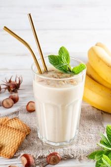 Здоровый завтрак. банановый смузи с печеньем в стакане, фруктами и печеньем из семечек, кунжута и меда