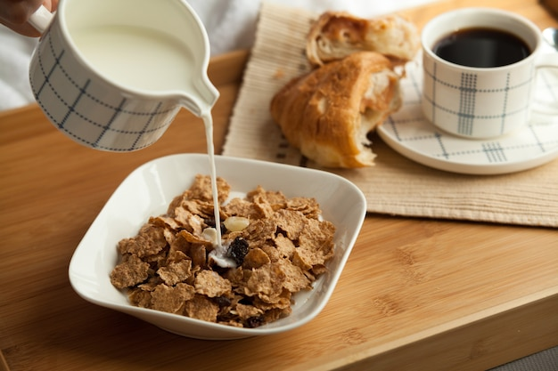 Healthy breakfast in bed with coffee and croissant, cornflakes with milk. hotel service.