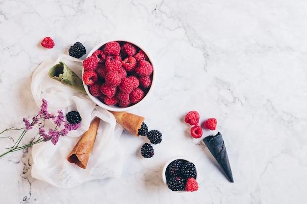 Здоровый завтрак. ежевика и малина, вафельный рожок мороженого и цветы на белом мраморном фоне. концепция здорового питания. вид сверху.