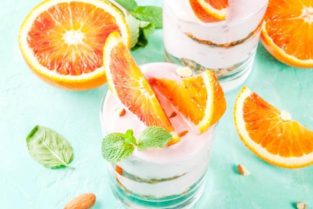 健康的な朝食、グラノーラとブラッドオレンジパフェ。ヨーグルト、アーモンドとミント、ライトブルー、copyspace