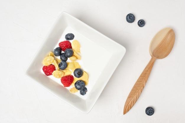 ホワイトボードにヘルシーな朝食用ボウル、コーンフレーク、ヨーグルト、新鮮なベリー。クローズアップ、上面図、孤立した背景。健康的でおいしい食べ物のコンセプト。