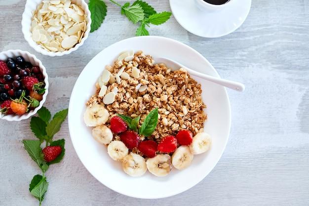 ヘルシーな朝食ボウル、新鮮なグラノーラ、ヨーグルトフルーツとコーヒーのミューズリー、イチゴ、白いテーブルの上のバナナ、上面図、コピースペース。きれいな食事、デトックス、ダイエット、ベジタリアンフードのコンセプト