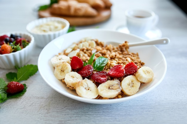 Healthy breakfast bowl, fresh granola, muesli with yogurt fruits and coffee, strawberry, banana on white table, copy space. clean eating, detox, dieting, vegetarian food concept