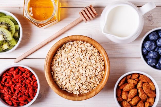 Здоровый завтрак - миска овсяных хлопьев со свежими фруктами, миндалем и медом