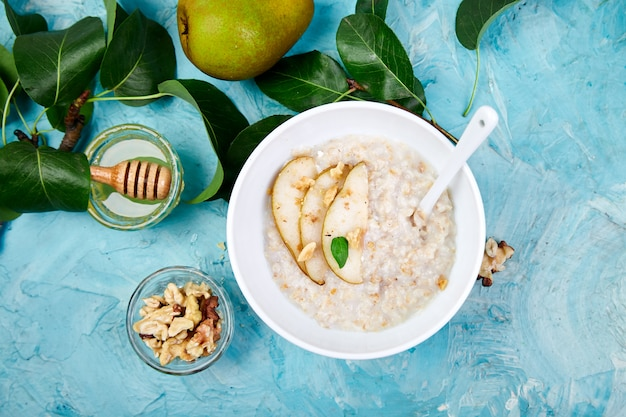 Healthy breakfast. a bowl of porridge with pears slices and walnuts on blue background.  flat lay. copy space. top view.