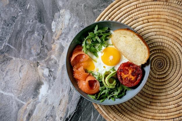 Миска для здорового завтрака с яичницей, лососем, авокадо, жареными помидорами и салатом с хлебом на соломенной салфетке. плоская планировка