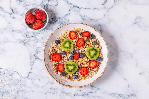 Здоровый завтрак, миска с овсяными мюсли и ягодами, вид сверху.
