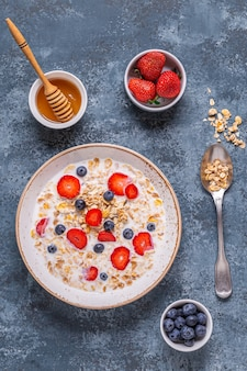 Healthy breakfast, bowl with oat granola, milk and berries, top view.