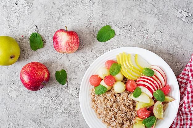 Здоровый завтрак. гречка или каша со свежей дыней, арбузом, яблоком и грушей. вкусная еда. вид сверху, копия пространства, плоская планировка