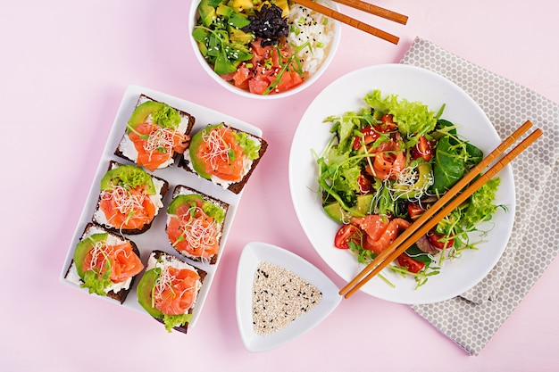 Healthy breakfast. buddha bowl with rice, mango, avocado and salmon and fresh salad with tomatoes, avocado, arugula, seeds, salmon and salmon sandwich with avocado, creame cheese and microgreen. healt
