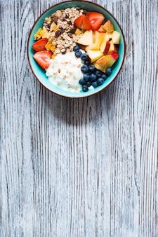 健康的な朝食、ヨーグルト、イチゴ、ブルーベリー、リンゴ、バナナ、素朴な木製の穀物。上面図