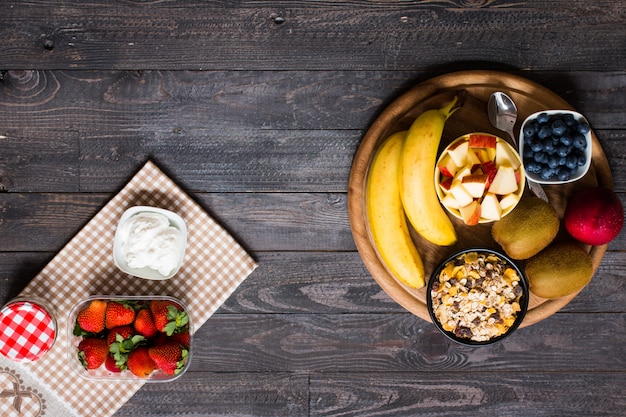 Healthy breakfast, cereal with yogurt, strawberries, blueberry, apple, banana, on rustic wooden.  top view
