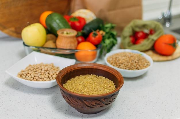Здоровые хлопья для завтрака, разные сырые хлопья, овощи, травы на кухонном столе, свежие сырые