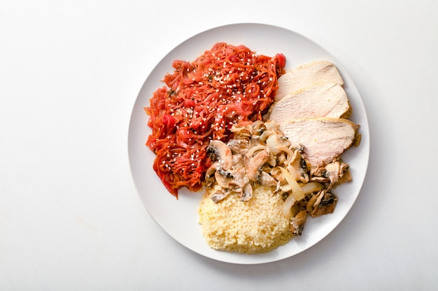 健康的な朝食。鶏ササミ、クスクス、野菜とキノコのシチュー、白い背景、上面図。